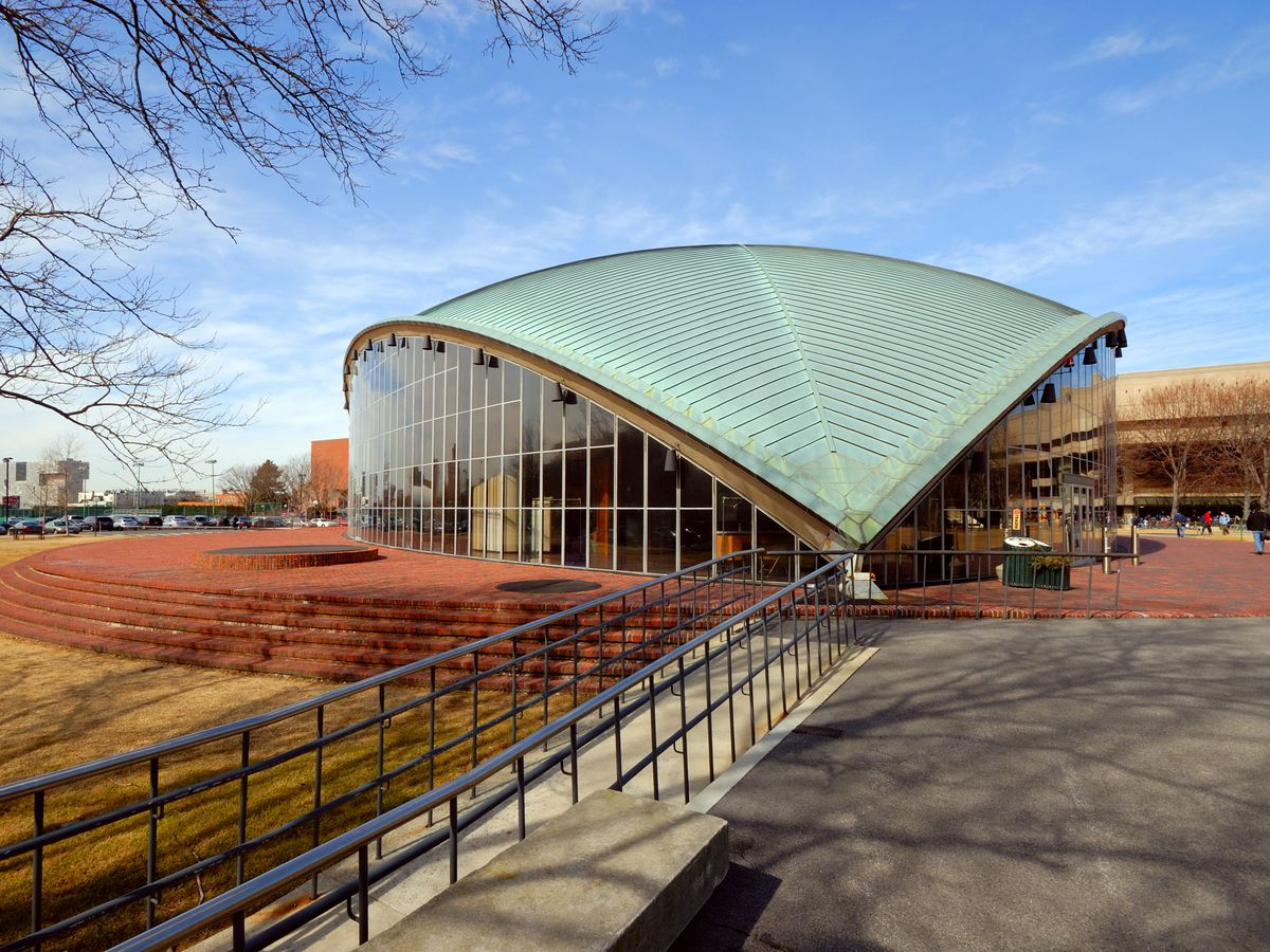 The exterior of the M.I.T. Auditorium. The roof is green and sloped.