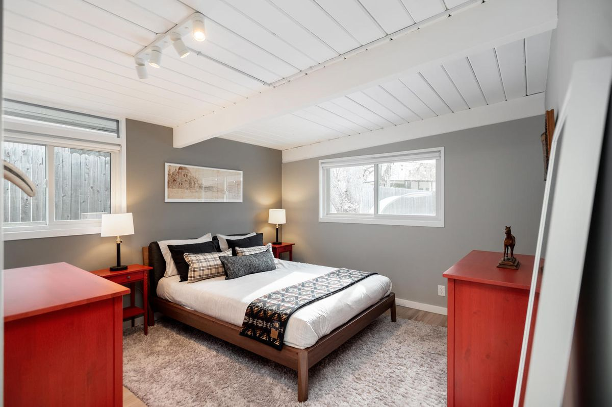 A wooden bed with white bedding has red accent furniture and gray walls.