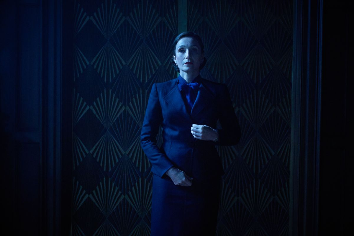 A woman in a dark suit stands in a dimly lit hallway in front of a door.