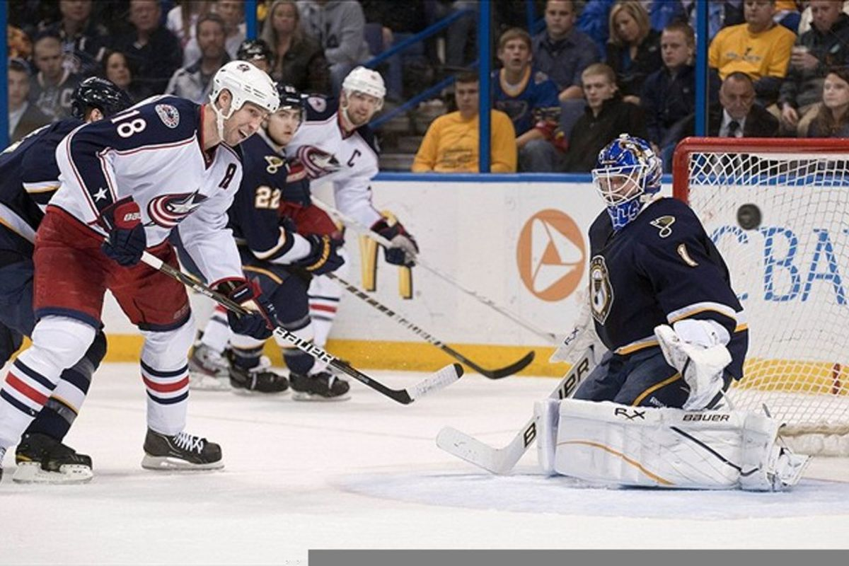 Mar 10, 2012; St. Louis, MO, USA; St. Louis Blues goalie Brian Elliott (1) deflects a shot from Columbus Blue Jackets left wing R.J. Umberger (18) during the second period at the Scottrade Center.  Mandatory Credit: Ed Szczepanski-US PRESSWIRE