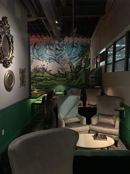 A lounge with silver wingback chairs inside Aunty Betty's Gin & Absinthe Bar  with a mural by Byran Stacy