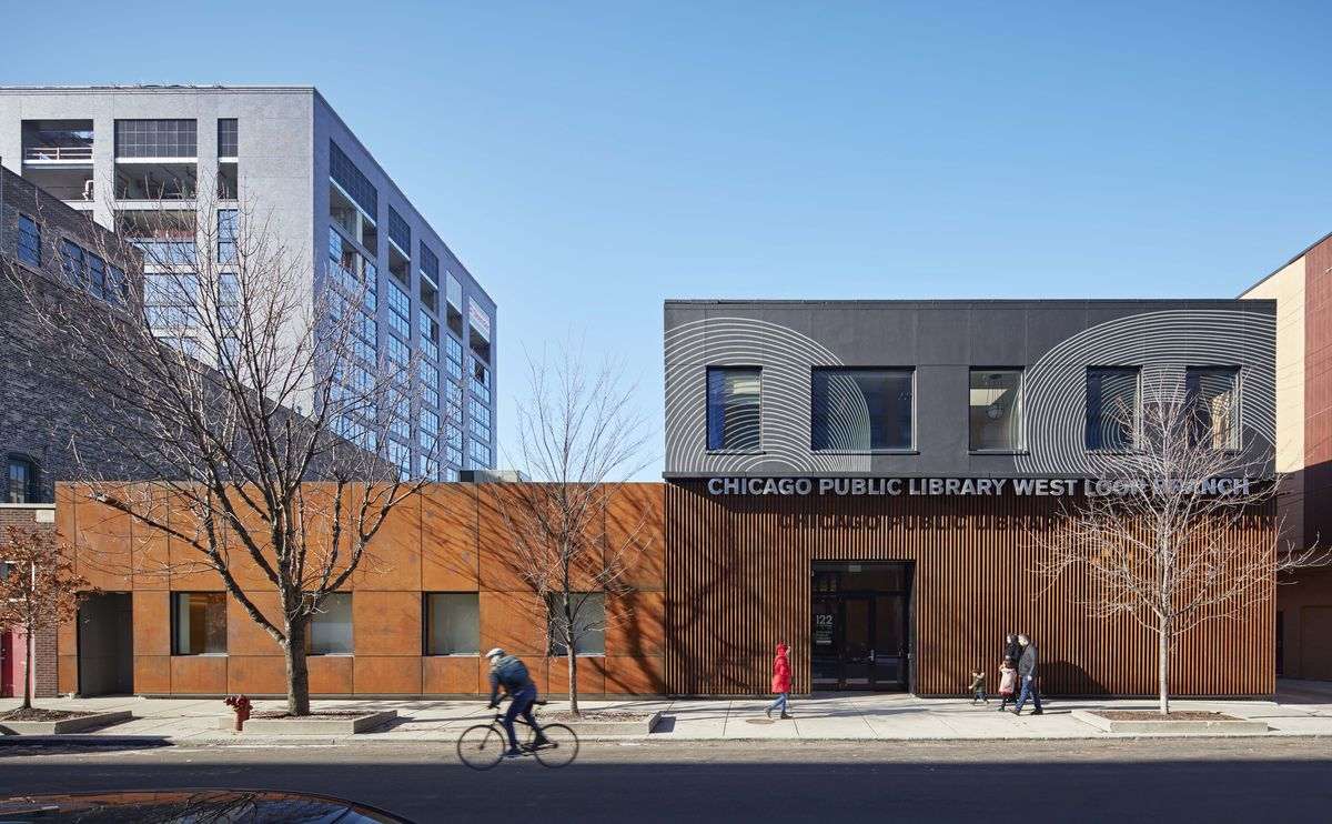 """A two story building with a brown metal exterior and square windows facing the street. A sign reads """"Chicago Public Library West Loop Branch."""""""