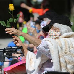 Ruth Torres holds a rose and waves at families as they pass residents at The Ridge Cottonwood senior living center in Holladay during a parade for Mother's Day on Saturday, May 9, 2020.