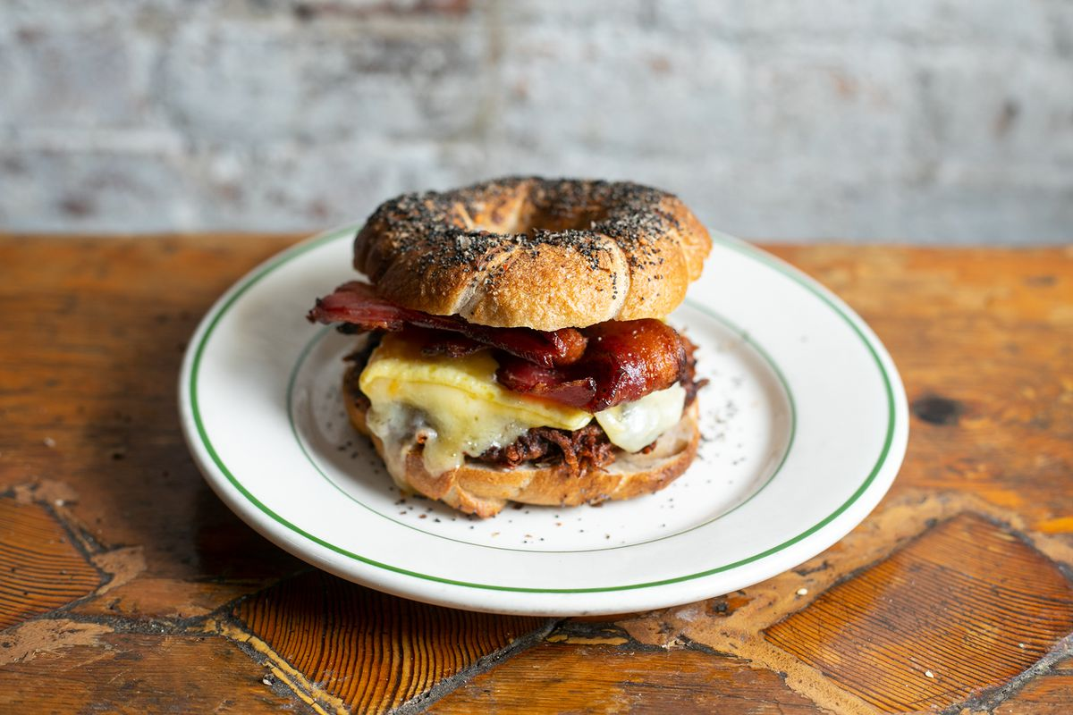 An everything bagel stuffed with bacon, egg, and a cheese latke, sits on a plate on a wooden counter