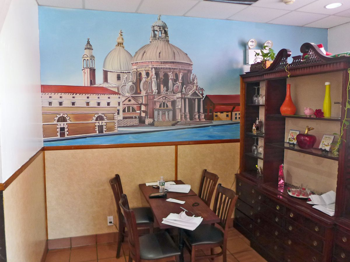 A wall mural of St. Marks in Venice with a table in front.