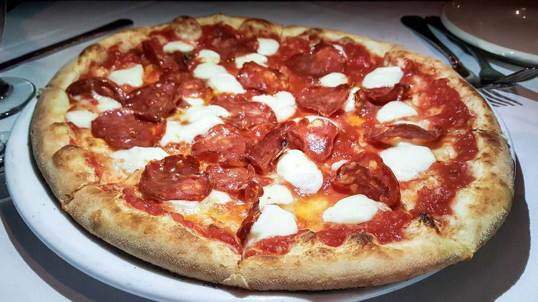 Pizza topped with pepperoni and blobs of mozzarella, served on a white plate on a table with a white tablecloth.