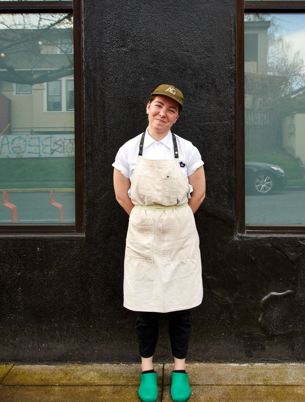 A woman with short hair and a brown cap stands outside a black building with her arms behind her back. She's wearing an off-white apron and bright aquamarine clogs.