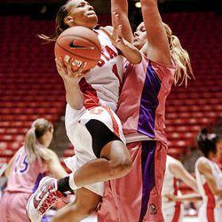 Utah's Janita Badon drives to the hoop against TCU's Helena Sverrisdottir as the University of Utah loses 105-96 to Texas Christian University in quadruple overtime at the Huntsman Center in Salt Lake City on Wednesday.
