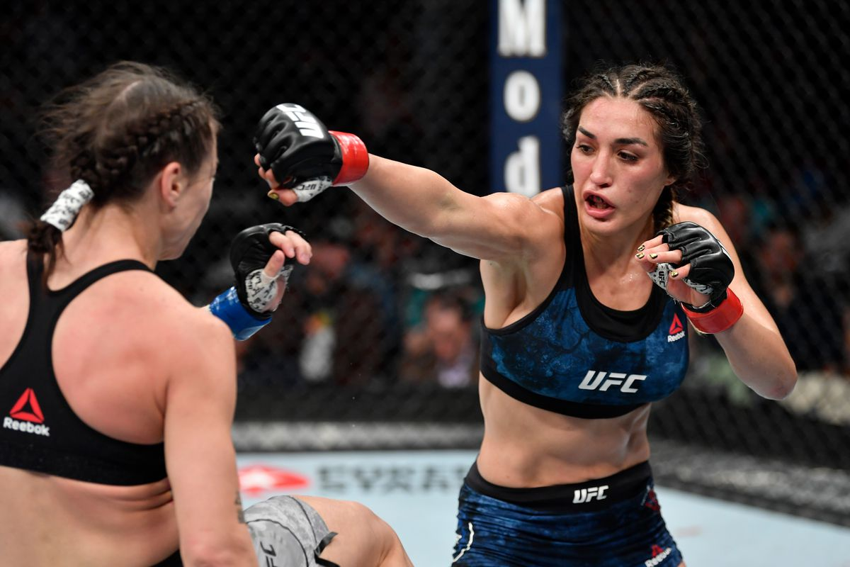Tatiana Suarez punches Nina Nunes in their women's strawweight bout during the UFC 238 event at the United Center on June 8, 2019 in Chicago, Illinois.