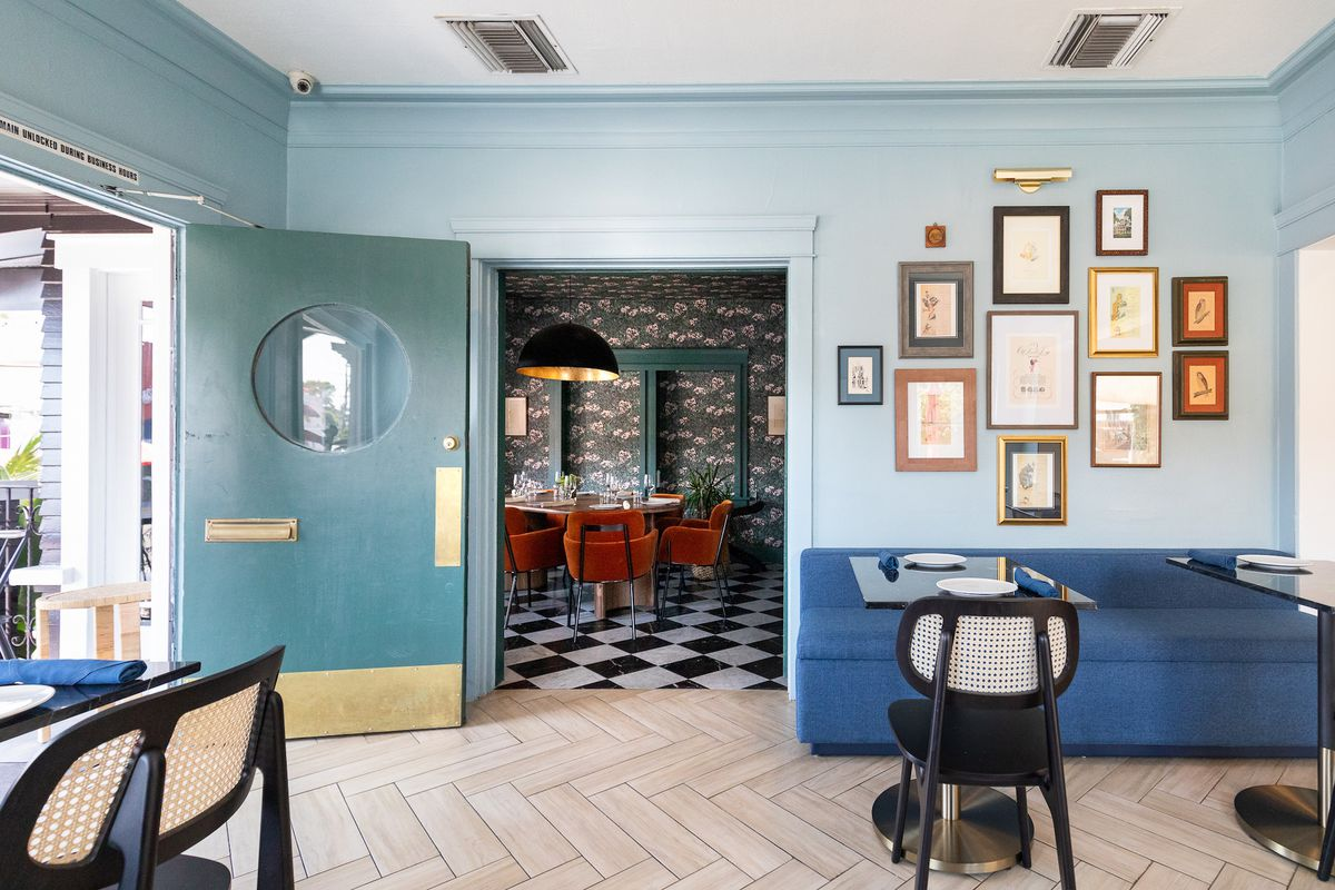 A light blue restaurant interior with open door and wooden floors.