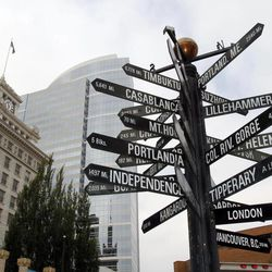 A sign with multiple worldwide destinations is shown in downtown Portland, Ore., Wednesday, Sept. 19, 2012.  Researchers at Portland State University found that the Portland atmosphere and culture is a magnet for the young and college educated, even though a disproportionate share of them are working in part-time jobs or positions that don't require a college degree.