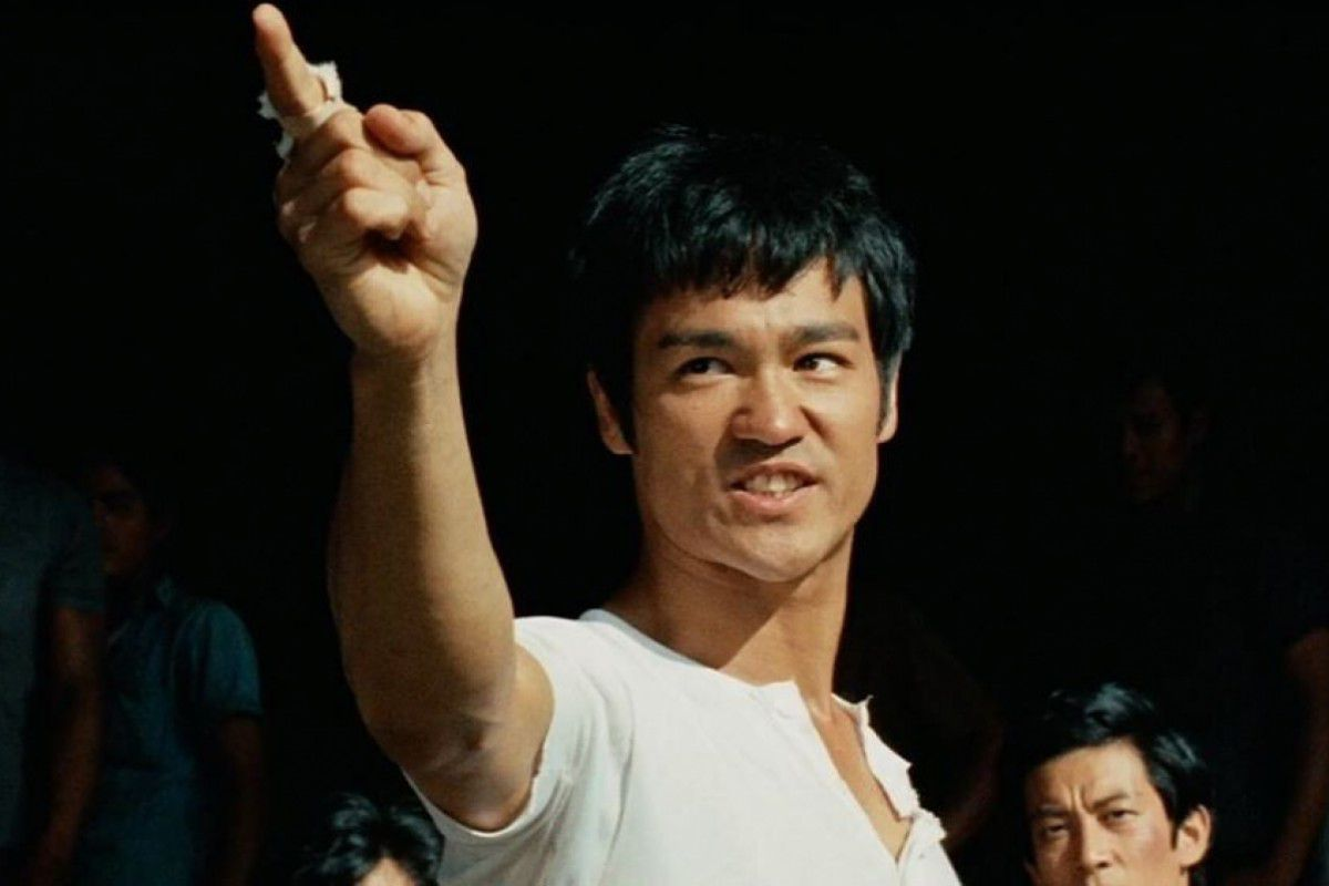 Bruce Lee points his fingers in the air while wearing a white t-shirt in The Big Boss