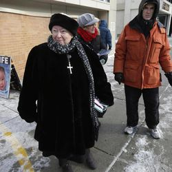 This photo taken Dec. 17, 2013 shows anti-abortion protester Eleanor McCullen, of Boston, left, standing at the painted edge of a buffer zone outside a Planned Parenthood location in Boston. With her pleasant demeanor and grandmotherly mien, McCullen has become the new face of a decades-old fight between abortion opponents asserting their right to try to change the minds of women seeking abortions and abortion providers claiming that patients should be able to enter their facilities without being impeded or harassed.   William Cotter of Operation Rescue looks on at right.
