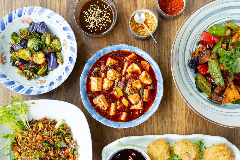 A variety of vegan dishes, including mapo tofu, sauteed brussels sprouts, and fried rice.