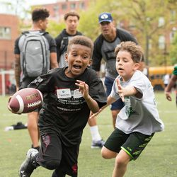 Harlem youth play football during a clinic staged by BYU players and coaches last weekend in New York.