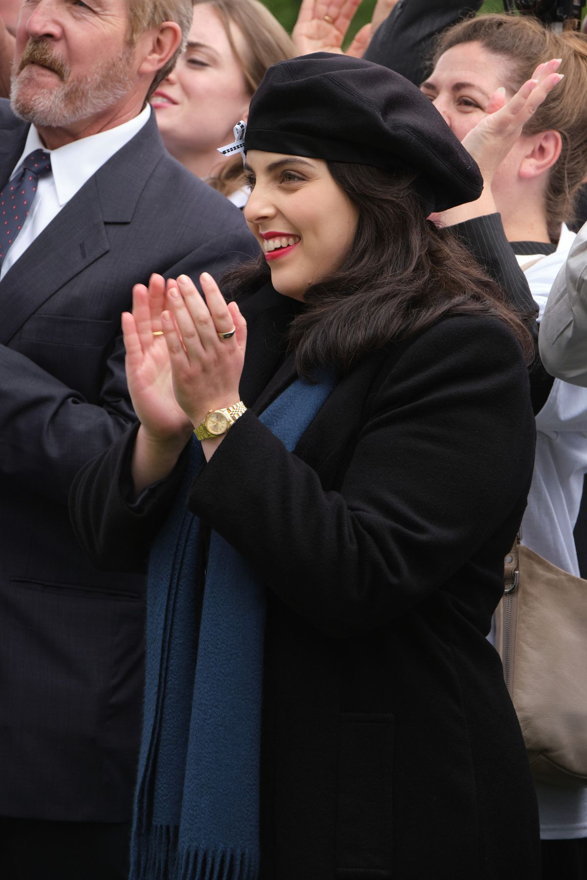 A dark-haired woman in a blue beret and red lipstick stands in a crowd, applauding an unseen figure.