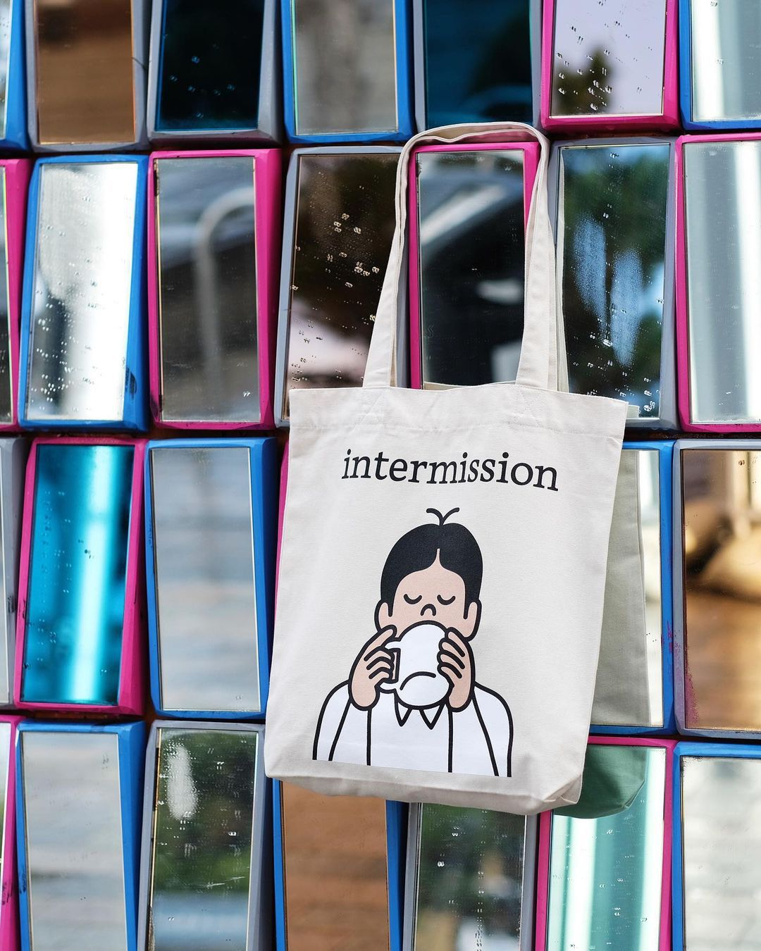 The best London restaurant merch to buy right now includes this tote bag with a cartoon man sipping coffee from Intermission