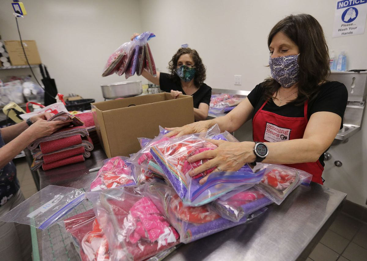 Pearl Boatright, Salt Lake County fiscal coordinator, and Linda Broussard, Salt Lake County Library senior human resources coordinator, organize face mask kits at the Viridian Library in West Jordan on Tuesday, July 7, 2020. Each kit contains supplies to make 20 masks. Salt Lake County and Stitching Hearts Worldwide have partnered to make 250,000 face masks with the help of volunteers.