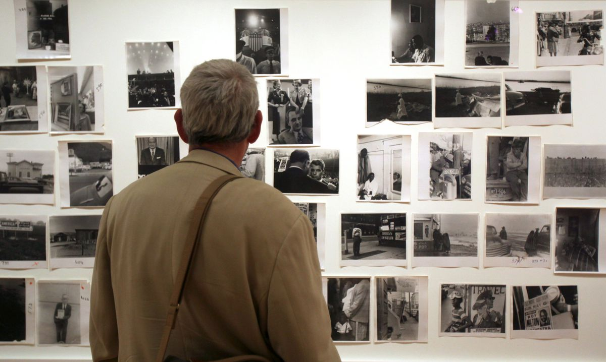 """In this 2009 file photo, a man looks at prints from the Looking In: Robert Frank's """"The Americans"""" exhibit at the Museum of Modern Art in San Francisco."""