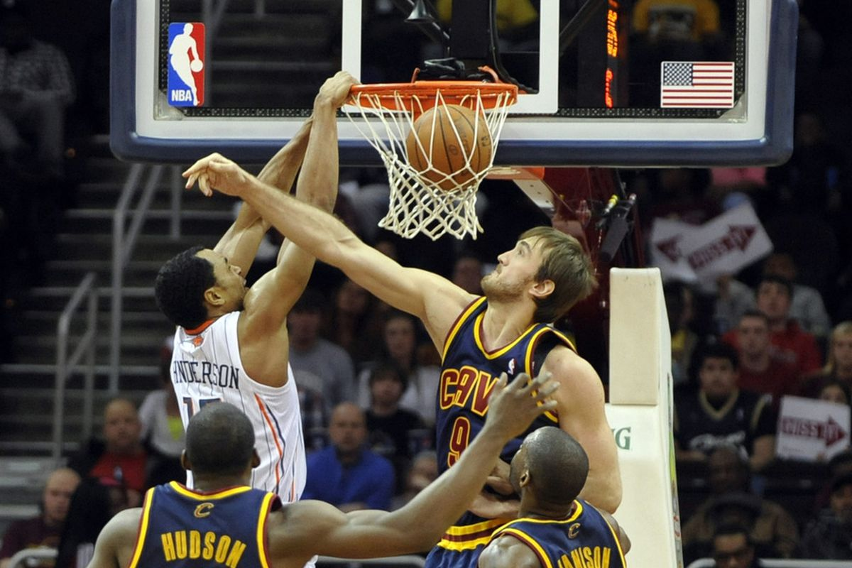 Apr 10, 2012; Cleveland, OH, USA; Charlotte Bobcats guard Gerald Henderson (left) dunks against Cleveland Cavaliers center Semih Erden (9) in the third quarter at Quicken Loans Arena. Mandatory Credit: David Richard-US PRESSWIRE