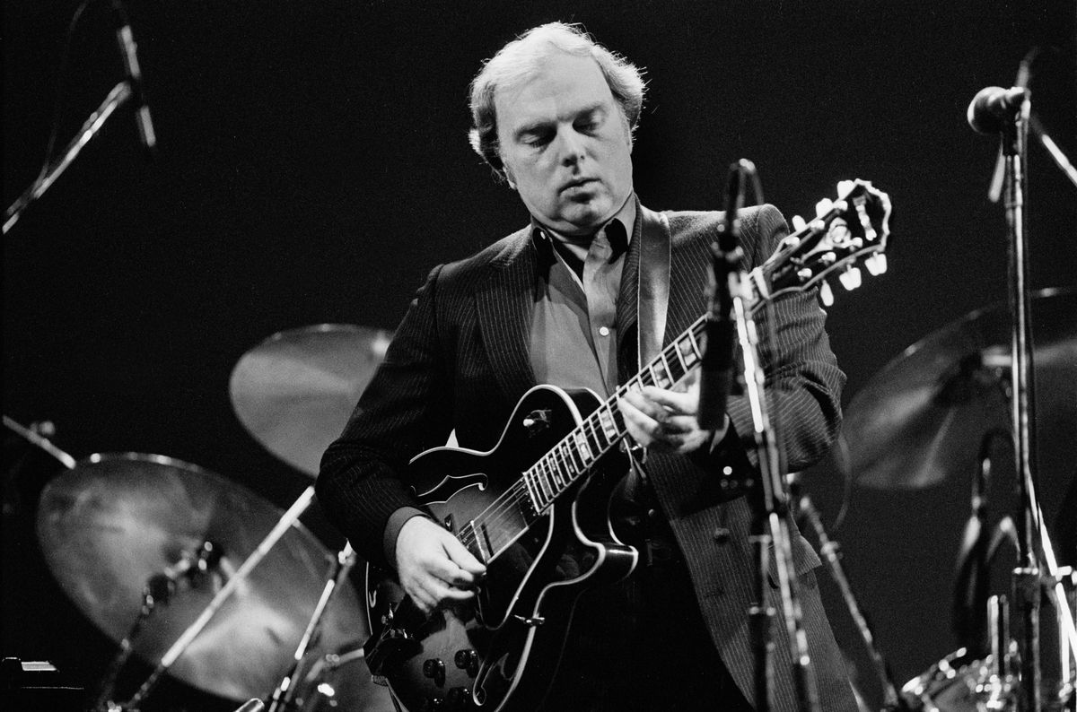 A black-and-white photo of Van Morrison playing guitar in front of a drum kit