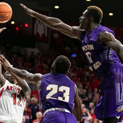 Arizona's Justin Coleman, far left, tries to float the ball in over Western New Mexico's Willie McCray (23) and Leston Gordon (12) during the Arizona-Western New Mexico University game in McKale Center on October 30 2018 in Tucson, Ariz.