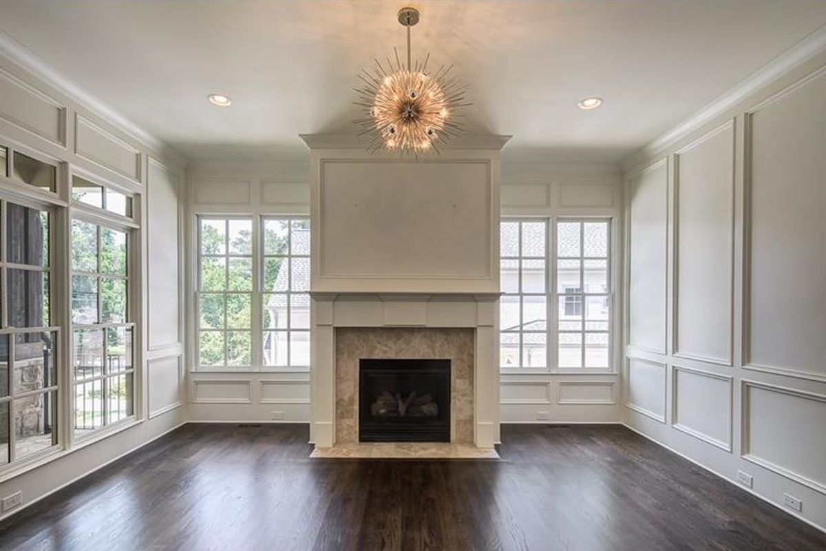A great room with fireplace and sunburst light fixture.