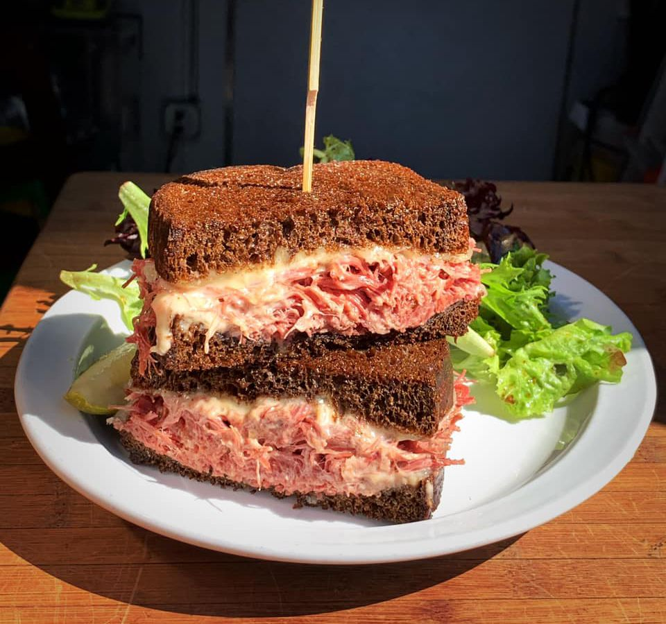 A sunbeam shines on a juicy pastrami on brown rye sandwich on a white plate