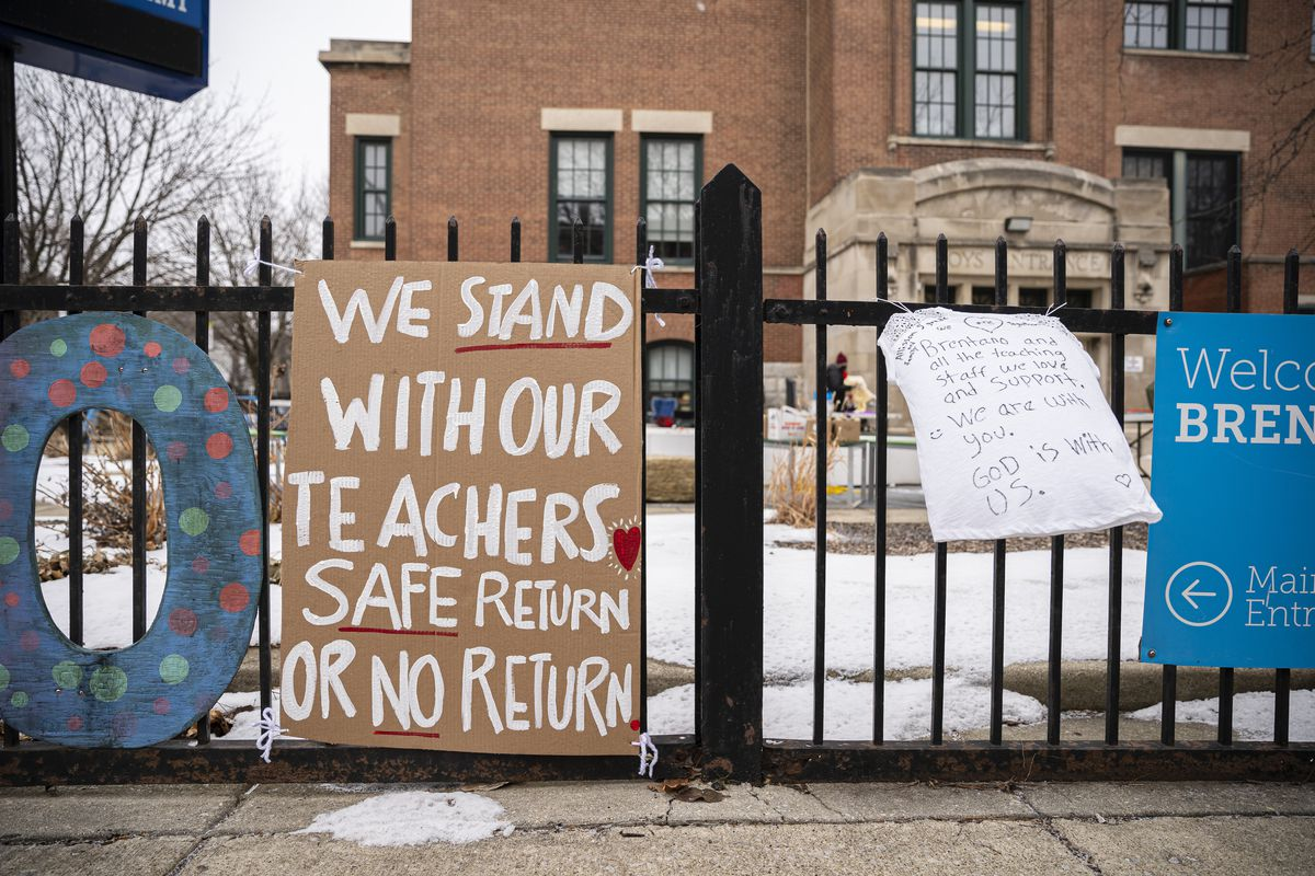 Banners in support of the elementary school teachers hang outside Brentano Elementary School as teachers instruct virtual classes during a protest against returning to in-person teaching outside of Brentano Elementary School in Chicago, Monday, Jan. 4, 2021.