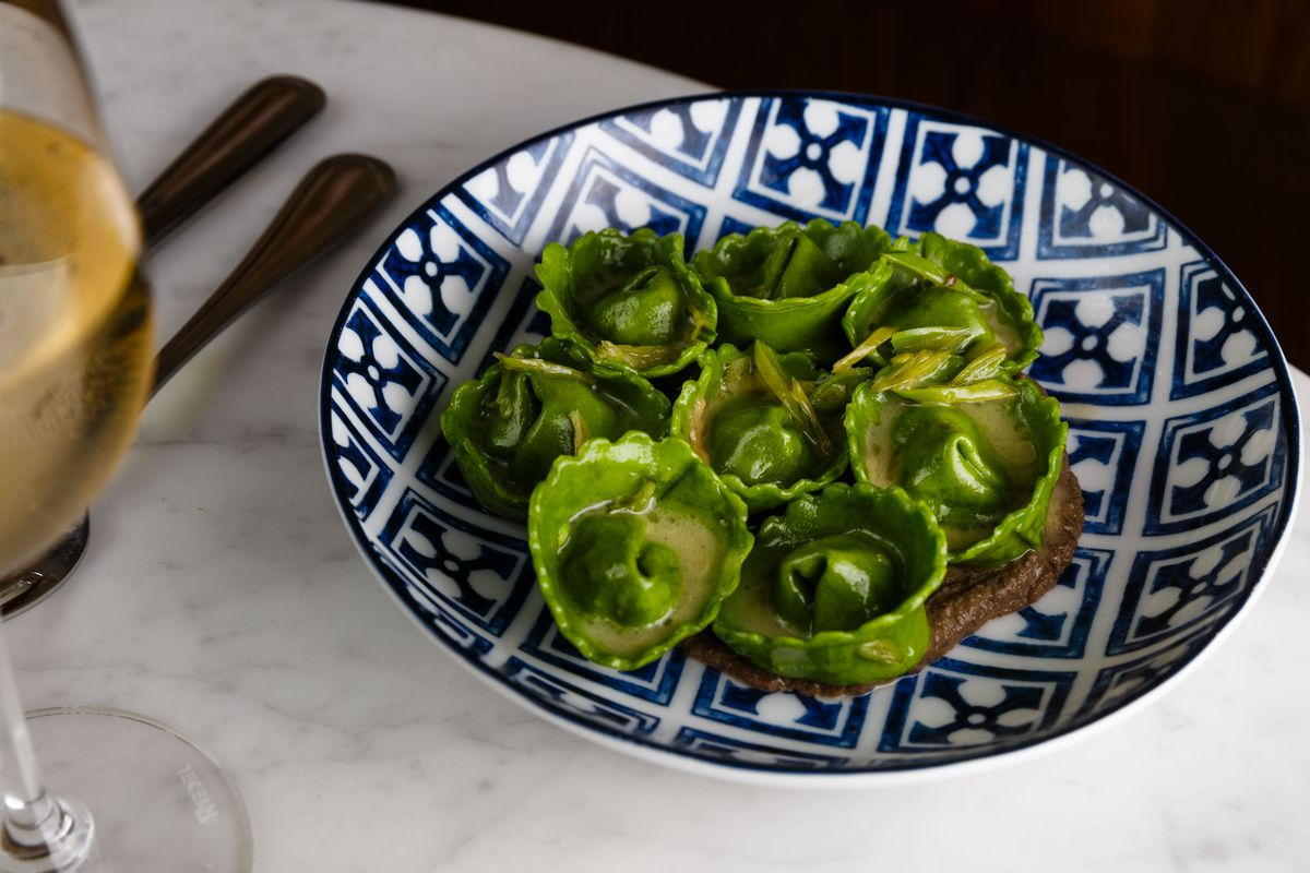 Green cappelleti pasta with spring peas and black mushroom puree on a blue-and-white checkered plate