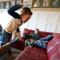 Max Widdison, 3, jumps onto the couch as his brother Isaac watches at their home in Saratoga Springs, Utah, Friday, Jan. 8, 2016.