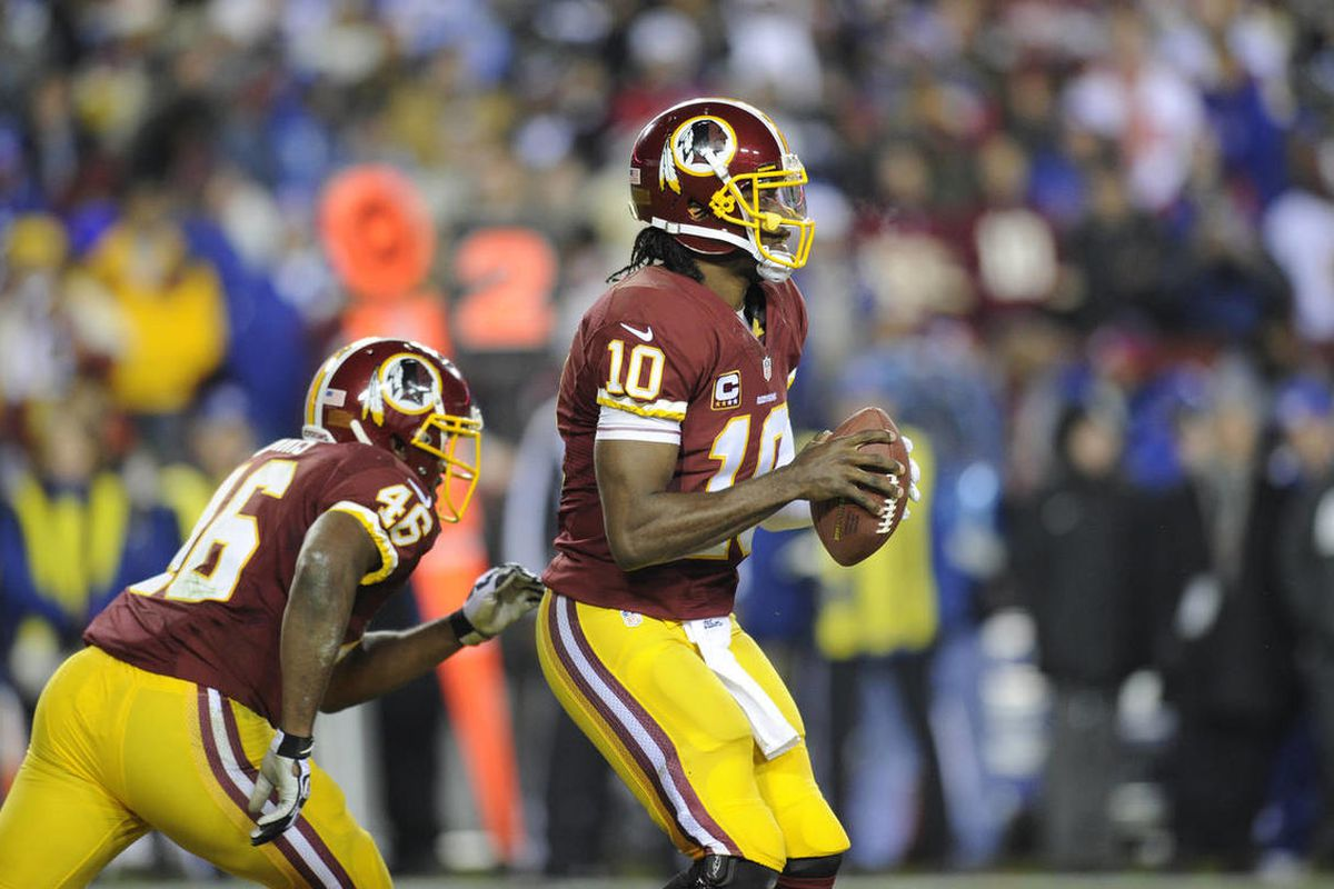 Washington Redskins quarterback Robert Griffin III (10) looks to pass against the New York Giants during the first half of an NFL football game Sunday, Dec. 1, 2013, in Landover, Md. The NFL's Washington Redskins, whose name and mascot have been sources o