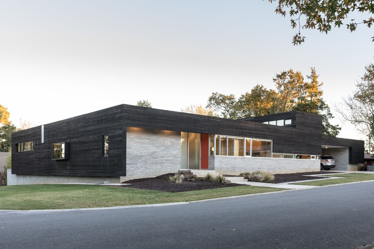 A single-story house with black siding and grey stone.