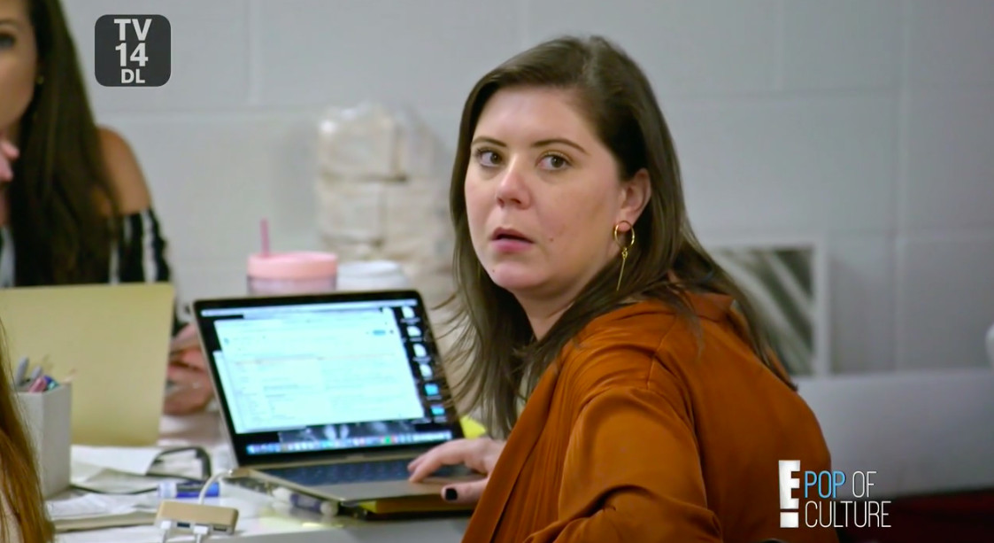 A woman turning around from her laptop screen, frowning