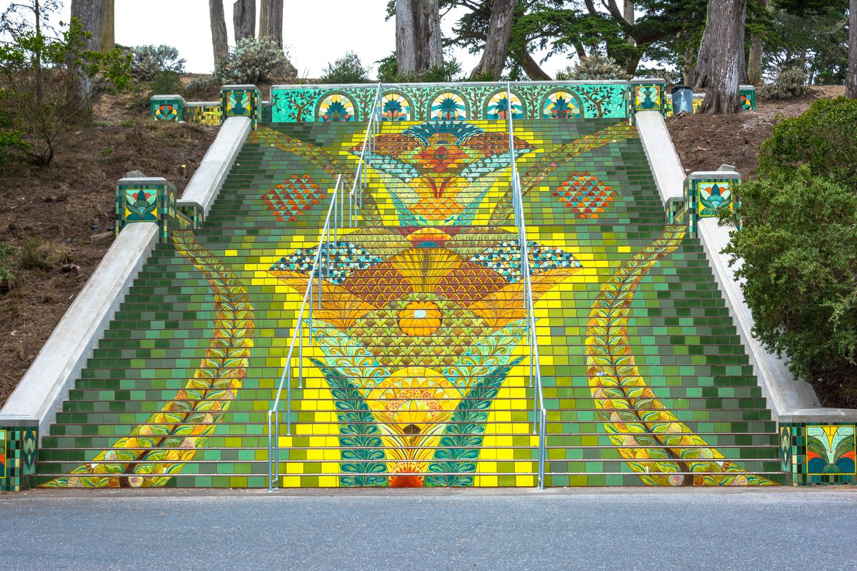 The Lincoln Park Steps featuring green, yellow, and orange mosaic tile work that makes up a floral patten. There are trees in the back, too.