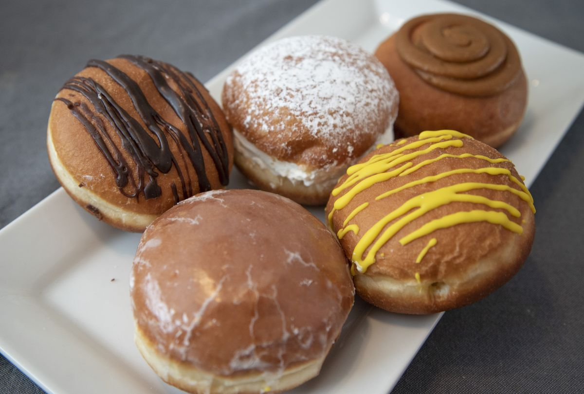 A white plate with five different paczki on it.