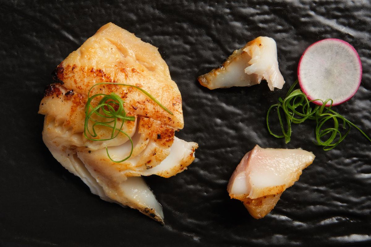 A piece of cooked black cod topped with scallion sits on a black stone surface next to two smaller pieces of fish and a slice of radish.