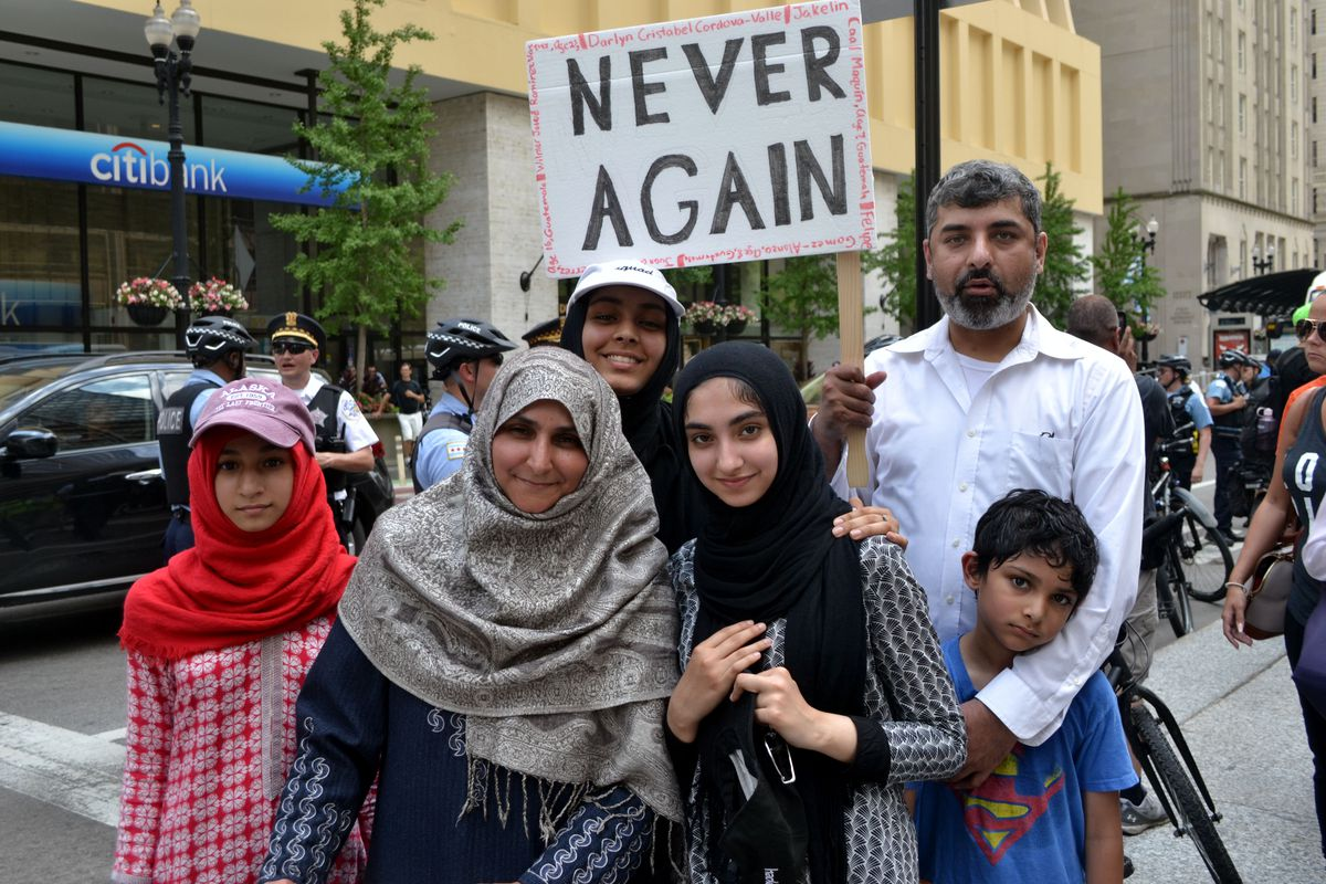 Bilal Mujahid (right) stands with his family Saturday at a rally in the Loop to show his support for immigrants.