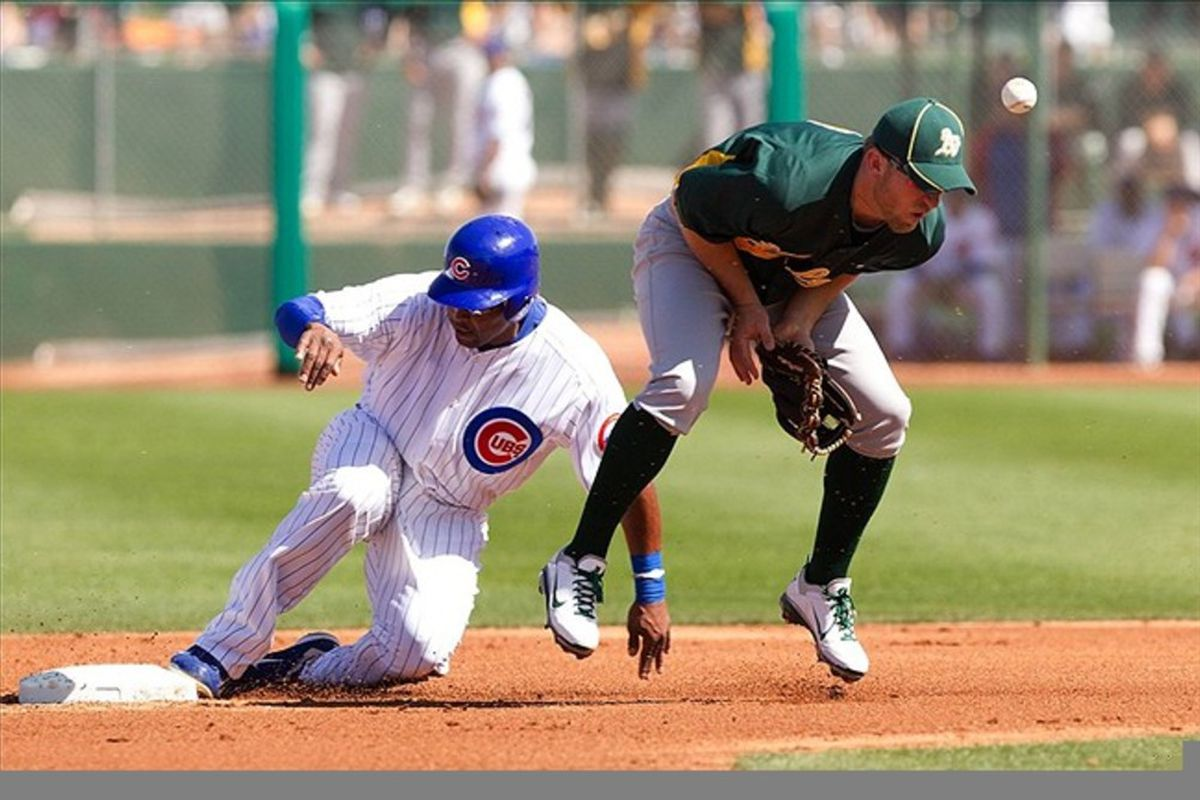 Chicago Cubs outfielder Marlon Byrd steals second base as Oakland Athletics infielder Eric Sogard bobbles the ball during a spring training game at HoHoKam Park. Credit: Allan Henry-US PRESSWIRE