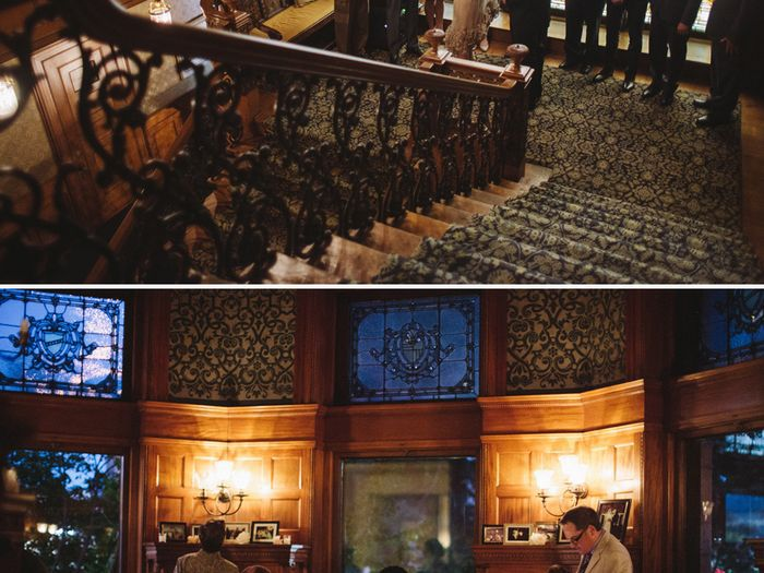 The interior of The Whitney in Detroit. There is a large staircase with patterned carpet and a wooden bannister.