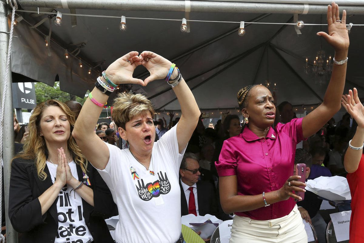 Barbara Poma, from left, owner of Pulse nightclub, Patty Sheehan, city commissioner, and Regina Hill, city commissioner, react during a public remembrance ceremony Monday, June 12, 2017, at Pulse nightclub in Orlando, Fla., in honor of the 49 people who l