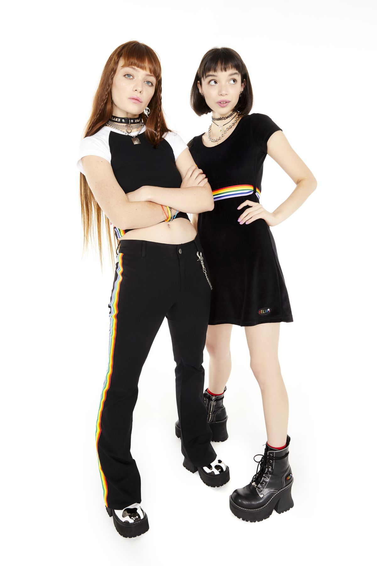 Two models wear black and rainbow outfits.