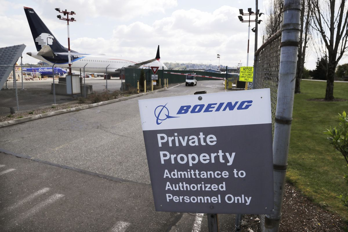 Planes sit parked behind a sign marking Boeing property at a Boeing production plant in Renton, Washington.