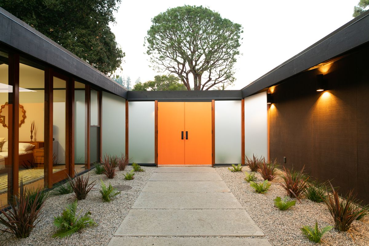 A path leading to an orange door. Walls of a house can be seen on either side of the door.