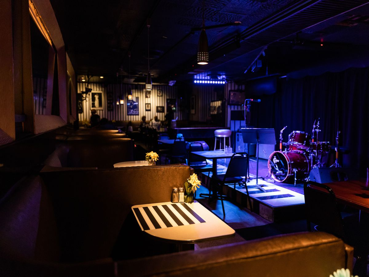 The dark dining room at Bakers Keyboard Lounge features black and white striped decor, purple lighting, and a stage with a drum kit.