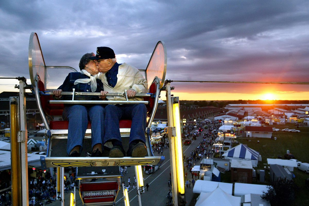Helen and Carroll Knoles of Springfield, ages 88 and 89, kiss on the ferris wheel at the Illinois State Fair as the Twilight Parade meanders through the fairgrounds in 2004, in Springfield.