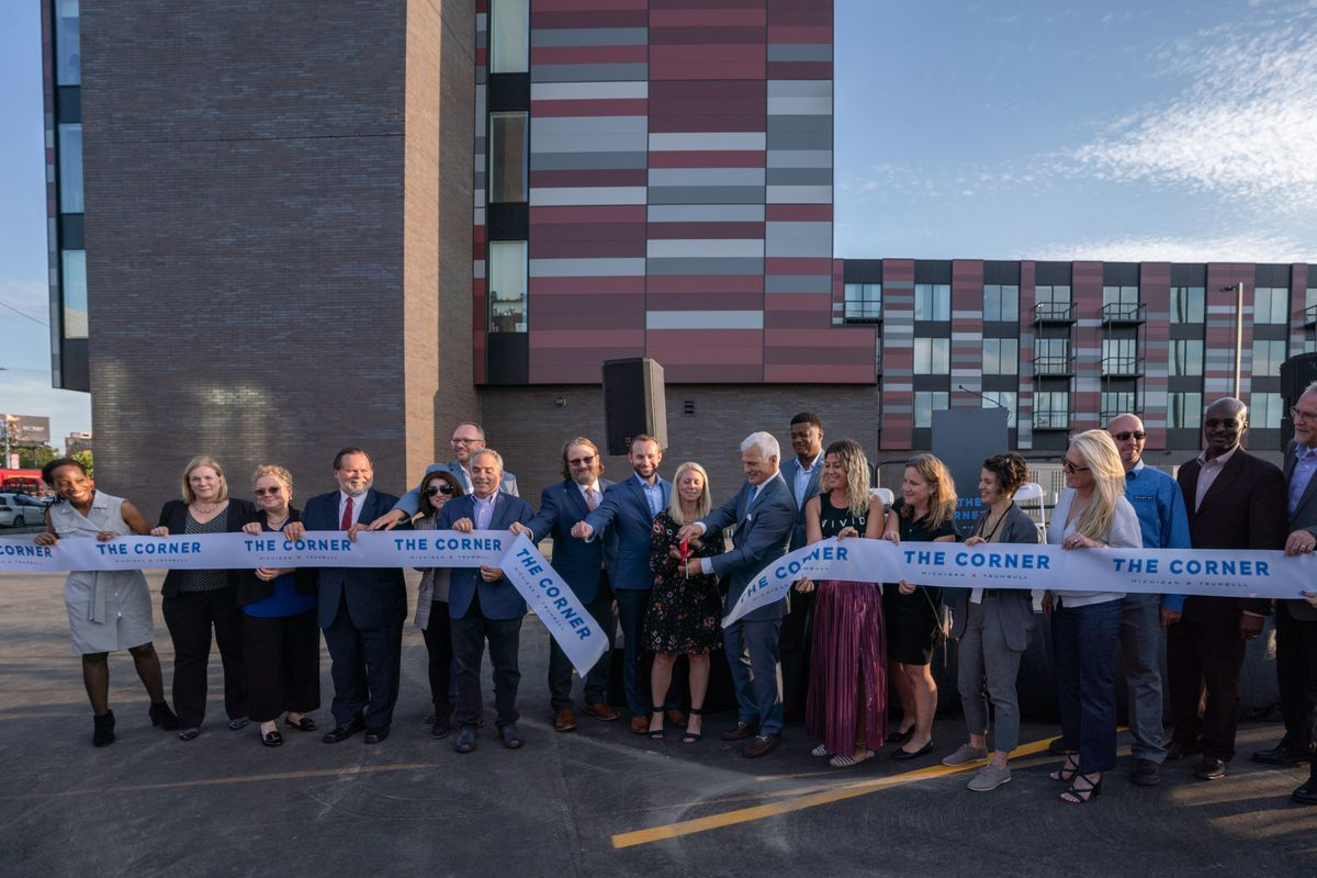 """A row of people in suits and professional attire stand behind a ribbon with """"The Corner"""" repeatedly written on it. Two people in front cut it with a pair of scissors. Behind them is a big brick building with windows and maroon and gray panelling."""