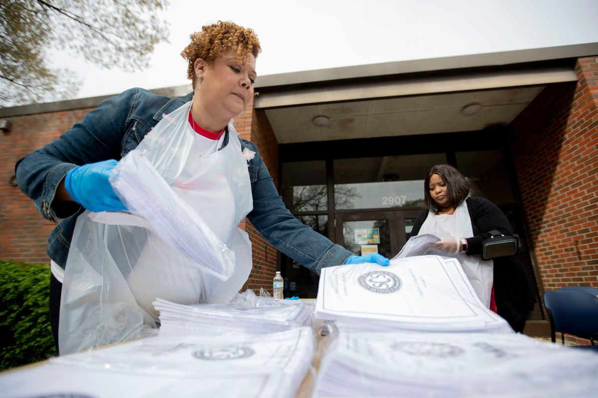 Shelby County Schools employees Randi Scott Howard (left) and Stacy Gibson spread out learning packets on a table at Ed Rice Community Center in Memphis.