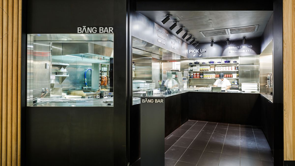 A look inside Bang Bar, with a black entrance and open kitchen within