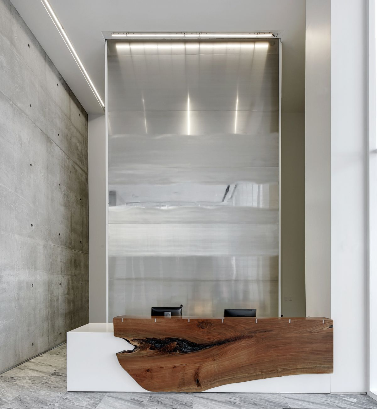 A two-story building lobby with raw concrete walls, marble floors, and a built-in white desk with a sculptural wooden front.